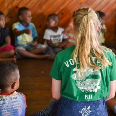 Childcare volunteer sits with her class in Fiji during her volunteer project abroad
